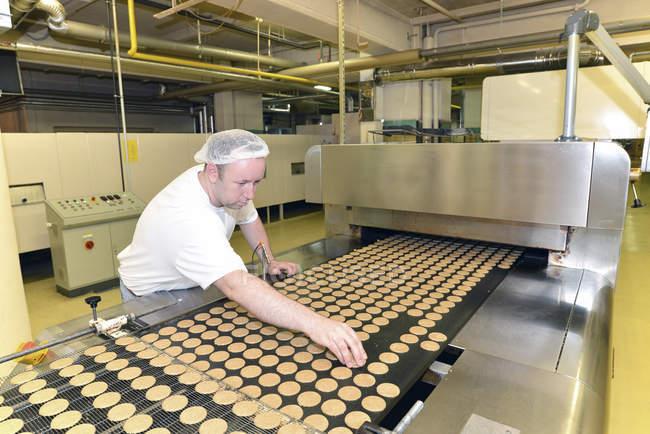 Людина, контролюючи печиво у випічки фабрика — стокове фото