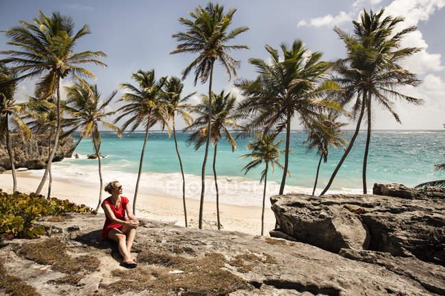 Caraïbes, la Barbade, la baie de fond, femme assise à la côte — Photo de stock