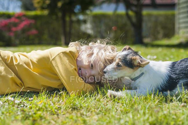 Garçon jouer avec Jack Russel Terrier chiot sur la pelouse dans le jardin — Photo de stock