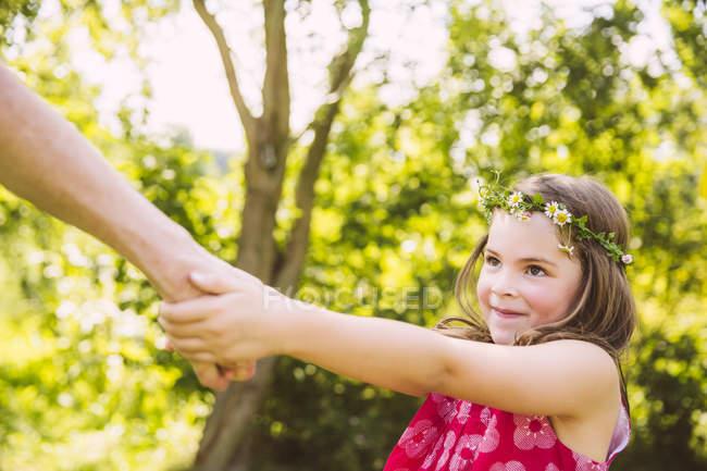 Девушка, потянув взрослых в руку в саду — стоковое фото