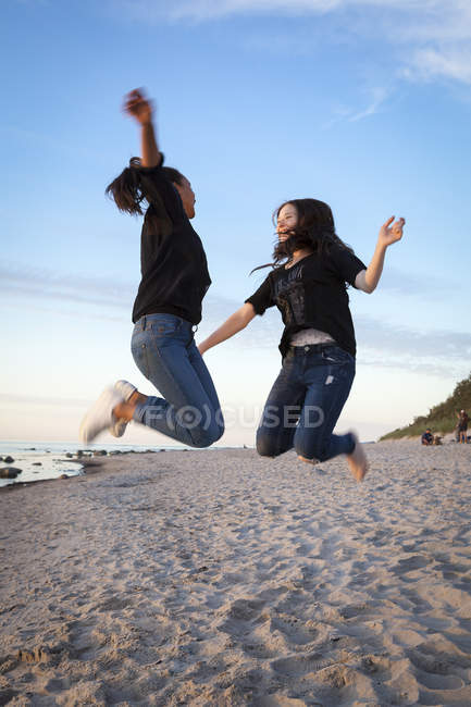 Germany, Ruegen, Two young female friends jumping at the beach — Stock Photo