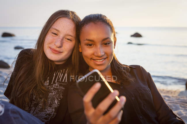 Two young female friends with smartphone at the beach — Stock Photo