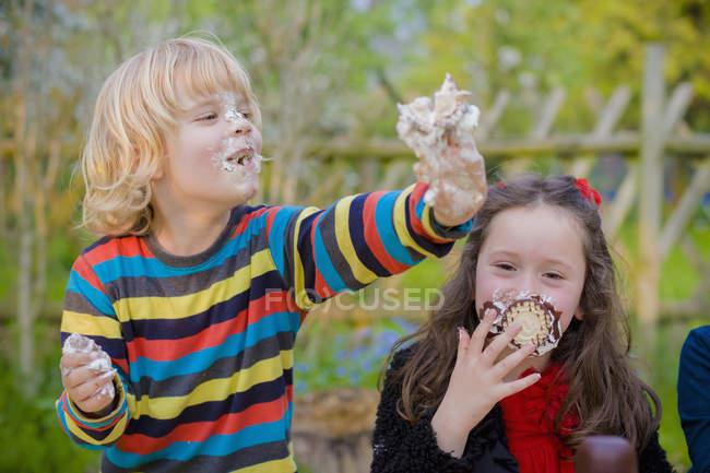 Bambini mangiare cioccolati caramelle gommosa e molle e scherzare — Foto stock