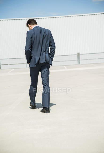 Ділова людина, ходьба на паркування рівня, вигляд ззаду — стокове фото