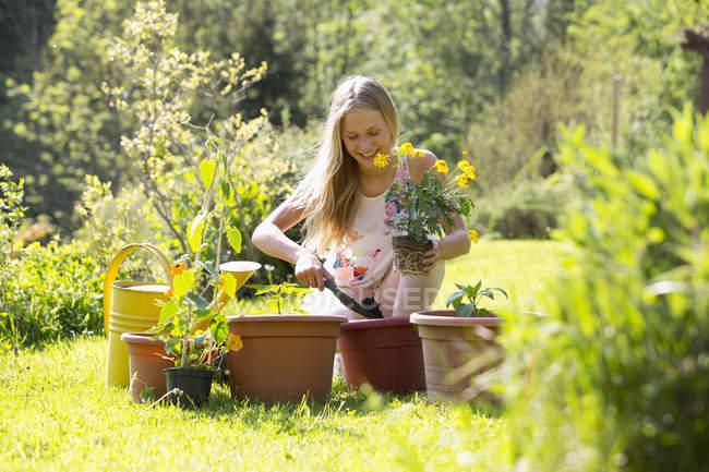 Smiling teenage girl potting plants in the garden — Stock Photo