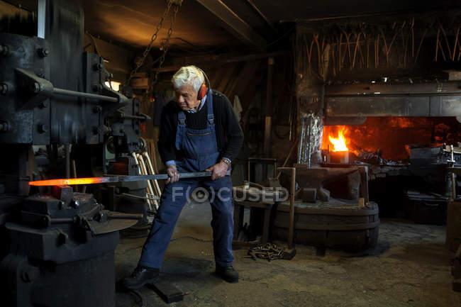 Germany, Bavaria, Josefsthal, senior  blacksmith at work in historic blacksmith's shop — Stock Photo