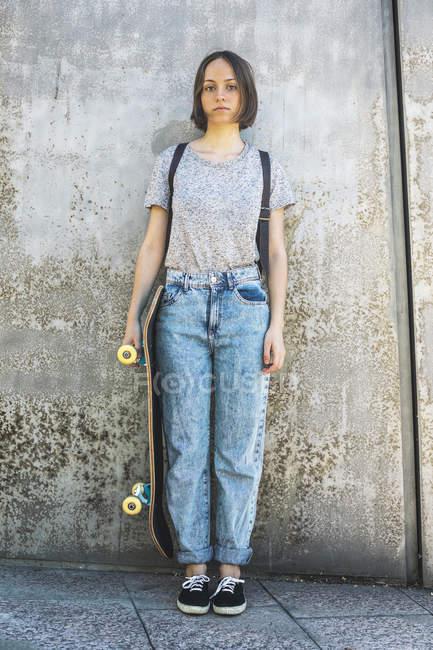 Pensionnaire de patinage femmes jeunes debout devant le mur — Photo de stock