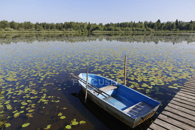 Germany, Bavaria, Freimoos, Lake Amerang and moored boat over water — Stock Photo