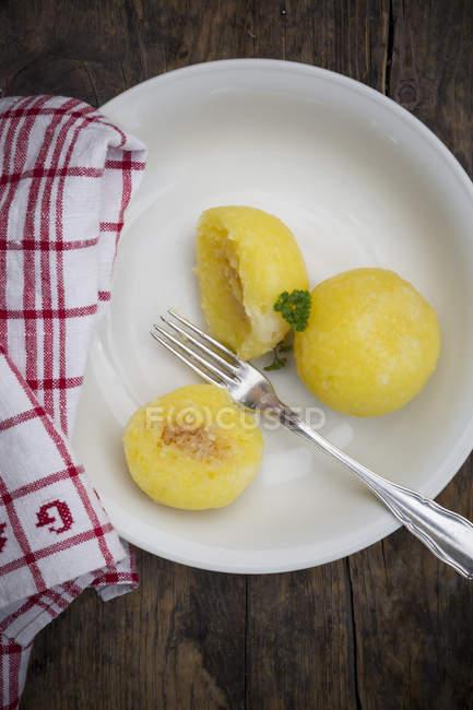 Ñoquis en el plato blanco con tenedor de madera oscura - foto de stock