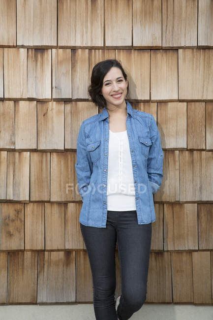 Portrait of young creative business woman in front of wood shingle panelling — Stock Photo