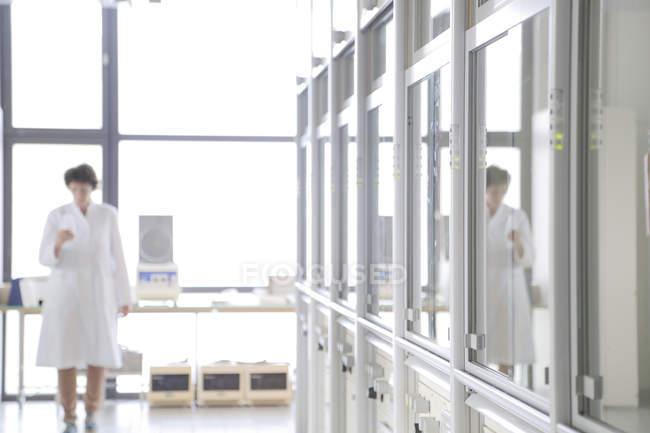 Female chemist in lab in laboratory coat — Stock Photo