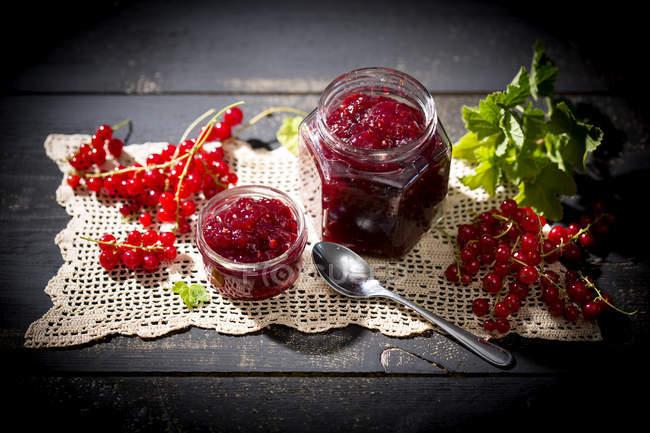 Варенье домашнее из красной смородины и свежей красной смородины на салфетка на темное дерево — стоковое фото