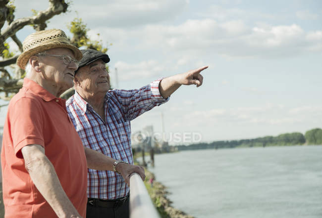 Two old men looking at river and pointing on something — Stock Photo