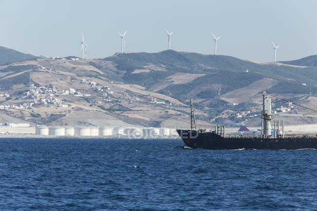 Marocco, Tangeri, Stretto di Gibilterra, Nave da carico, Parco eolico e raffineria sulla costa — Foto stock