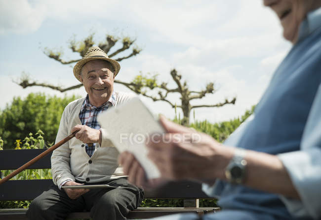 Two old senior friends using digital tablets at park — Stock Photo