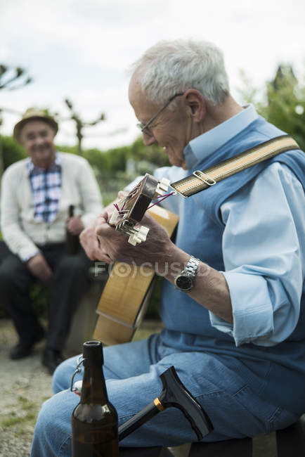 Two old men with guitar in the park — Stock Photo
