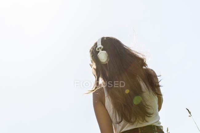 Giovane donna con le cuffie davanti al cielo, vista posteriore — Foto stock