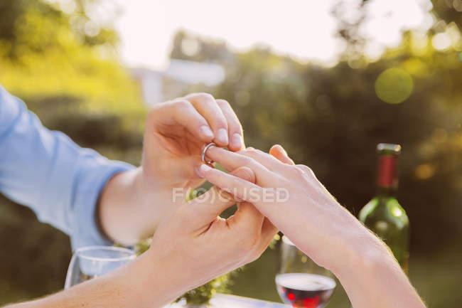 Menschen Sie setzen Ring an Frau Finger beim Abendessen — Stockfoto