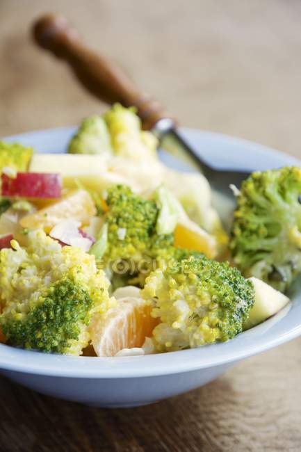 Salad with broccoli, apple, clementines, almond flakes and miso dressing in bowl — Stock Photo