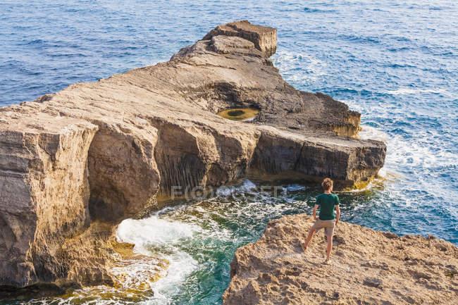 Grèce, îles de la mer Égée, Rhodes, jeune homme debout sur l'îlot rocheux — Photo de stock