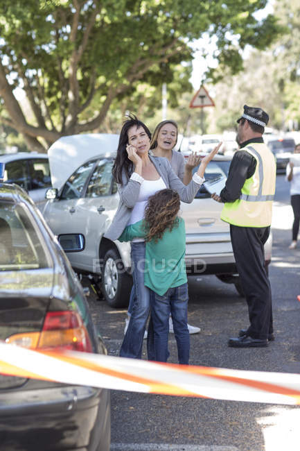 People and policeman at car accident scene — Stock Photo