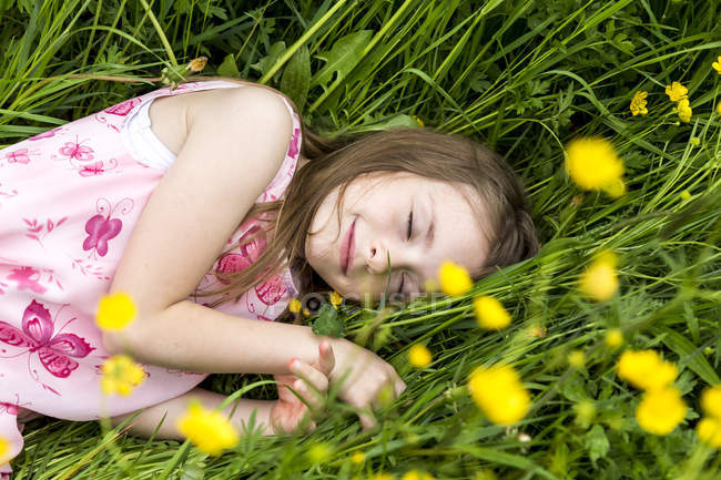 Smiling little girl with closed eyes lying on a flower meadow — Stock Photo