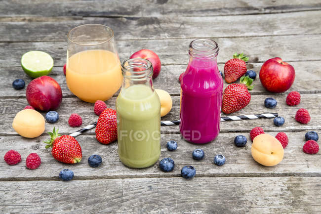 Different fruit smoothies and fresh fruits on grey wooden surface — Stock Photo