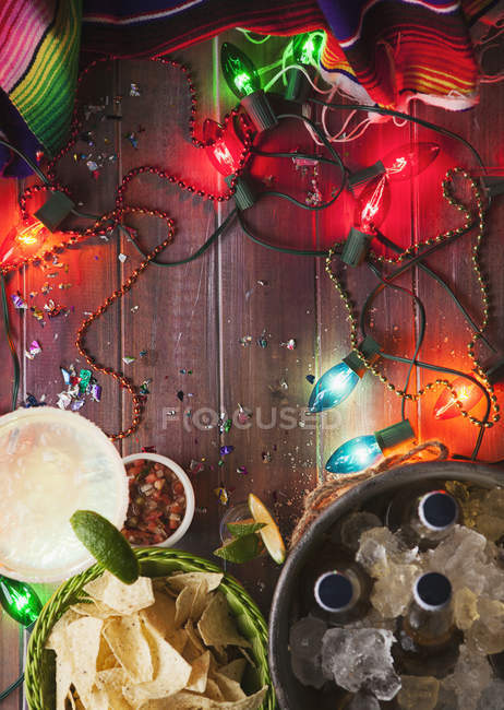 Top view of beer bottles in ice with tortilla chips and fairy lights on wooden background — Stock Photo