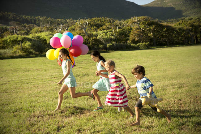 Happy children running with balloons on meadow — Stock Photo