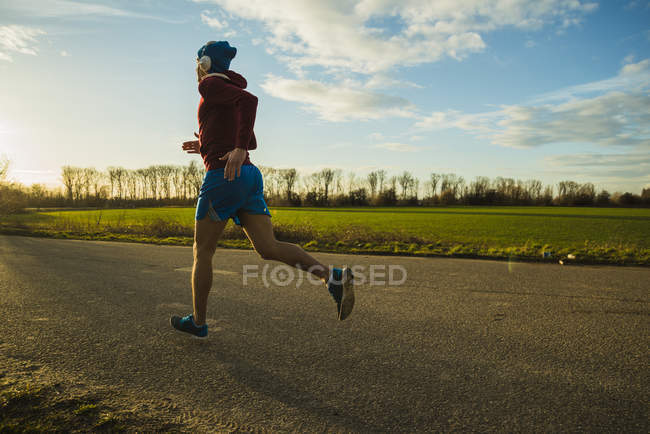 Young man jogging on rural road — Stock Photo