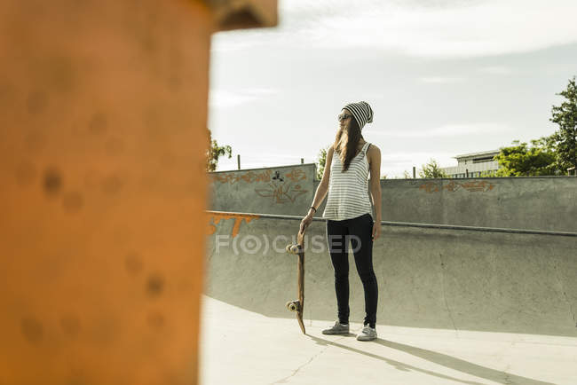 Young skate boarder wearing sunglasses and cap standing in a skatepark — Stock Photo