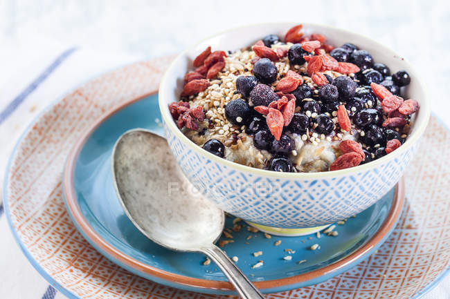 Vegan суперпродукт сніданок з каша мигдальне молоко, чорниця, смажені квіноа та годжі ягоди — стокове фото