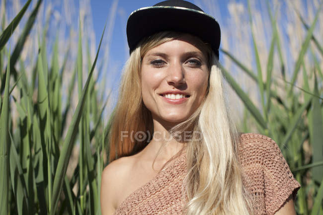 Portrait of smiling young woman wearing baseball cap — Stock Photo