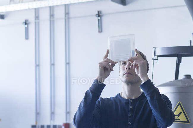 Technician in workshop examining sample — Stock Photo