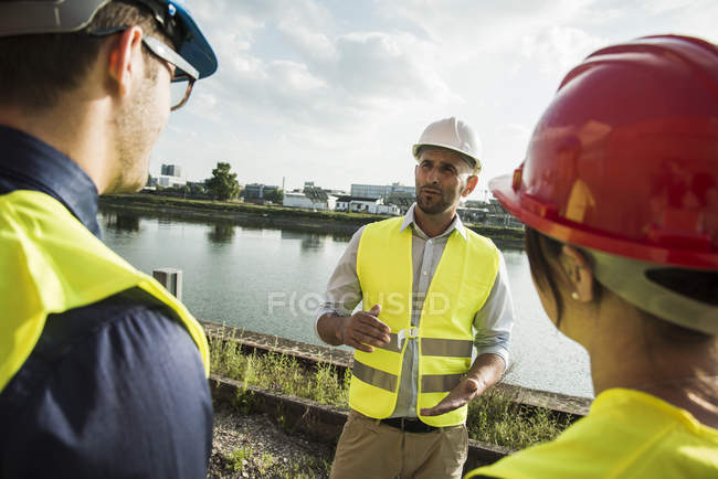 Woman and two men with safety helmets talking at riverside — Stock Photo