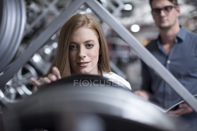 Female customer inspecting a tyre in a tyre shop — Stock Photo