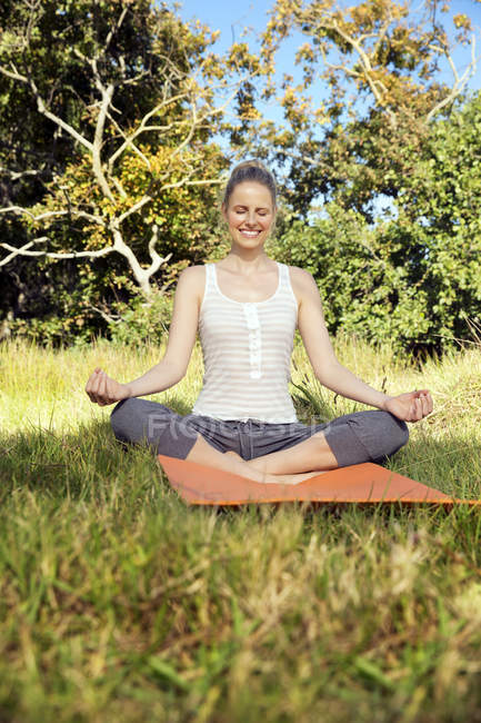 Smiling woman practising yoga in a meadow — Stock Photo