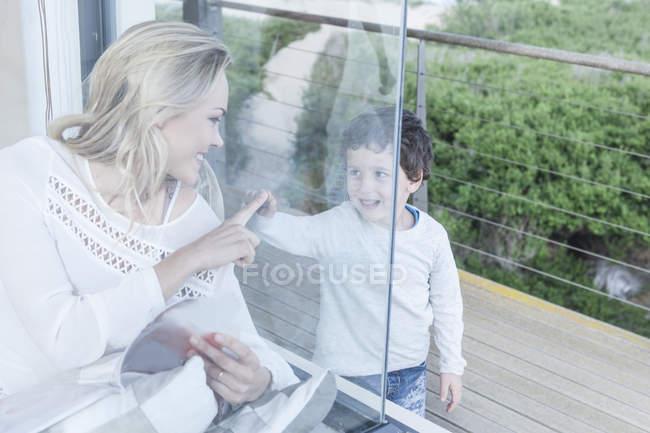 Sorridente madre e figlio dietro il vetro della finestra — Foto stock