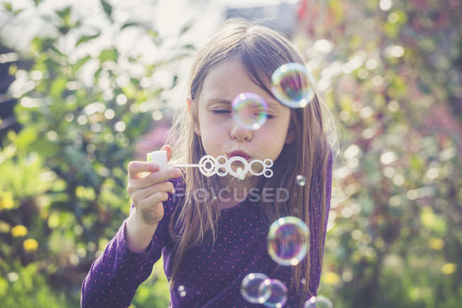 Girl blowing soap bubbles in a garden — Stock Photo