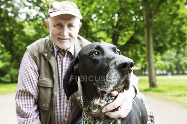 Портрет старшого чоловіка зі своєю собакою Shorthaired Німецька жорсткошерстна лягава в міському парку — стокове фото