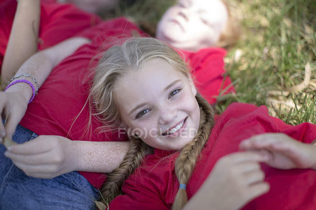 Portrait of smiling girls lying on grass — Stock Photo