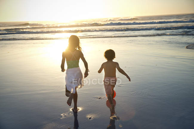 Boy and girl running on beach at sunset — Stock Photo