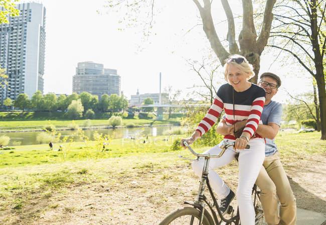 Літня пара верхової їзди велосипеді в парку, людина сидить на стійку — стокове фото