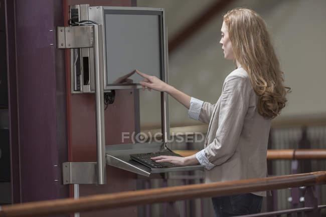 Студентка с сенсорным экраном в библиотеке — стоковое фото