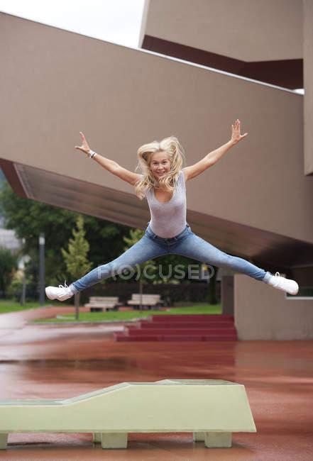 Porträt von blonde Teenager-Mädchen mit ausgestreckten Armen und Beinen in der Luft springen — Stockfoto