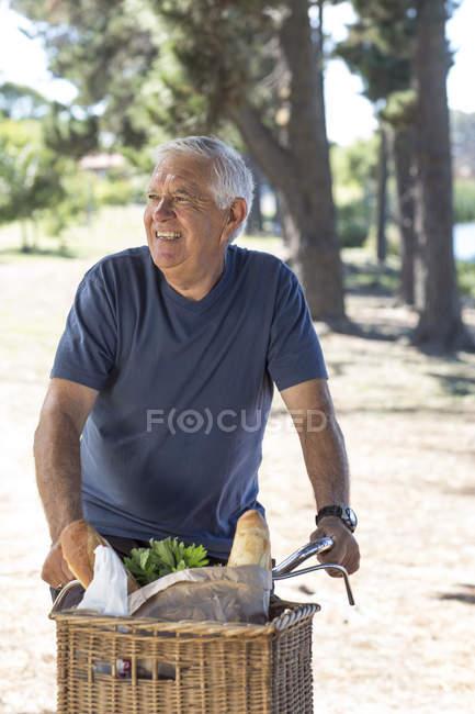 Smiling senior man on bicycle — Stock Photo