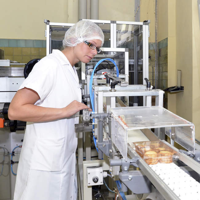 Woman controlling production line in a baking factory — Stock Photo