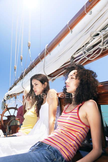 Trois jeunes femmes détendues sur un voilier — Photo de stock