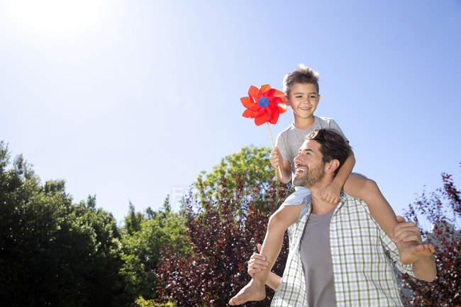 Батько несучи сина на плечі — стокове фото