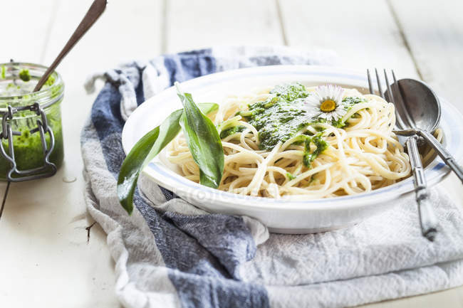 Spaghetti with ramsons pesto and wild garlic leaves, kitchen towel on wooden table — Stock Photo